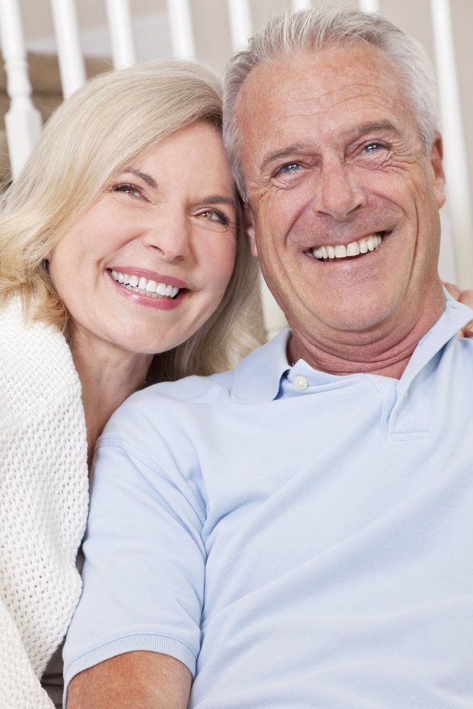 Happy man and woman couple sitting together at home