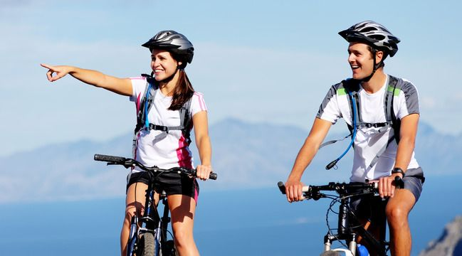 An adventurous couple riding bikes.