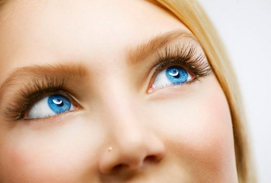 A blonde woman with bright blue eyes and a discreet nose ring looks up.