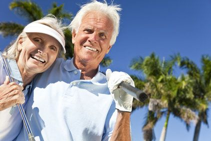 A smiling elderly couple in golf attire.