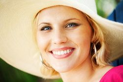 A woman wearing a sun hat and smiling broadly, showing off her white, stain-free teeth