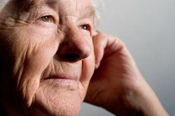 Pensive-looking elderly woman with hand against cheek