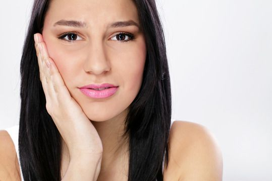 Pretty Hispanic woman holding jaw in pain