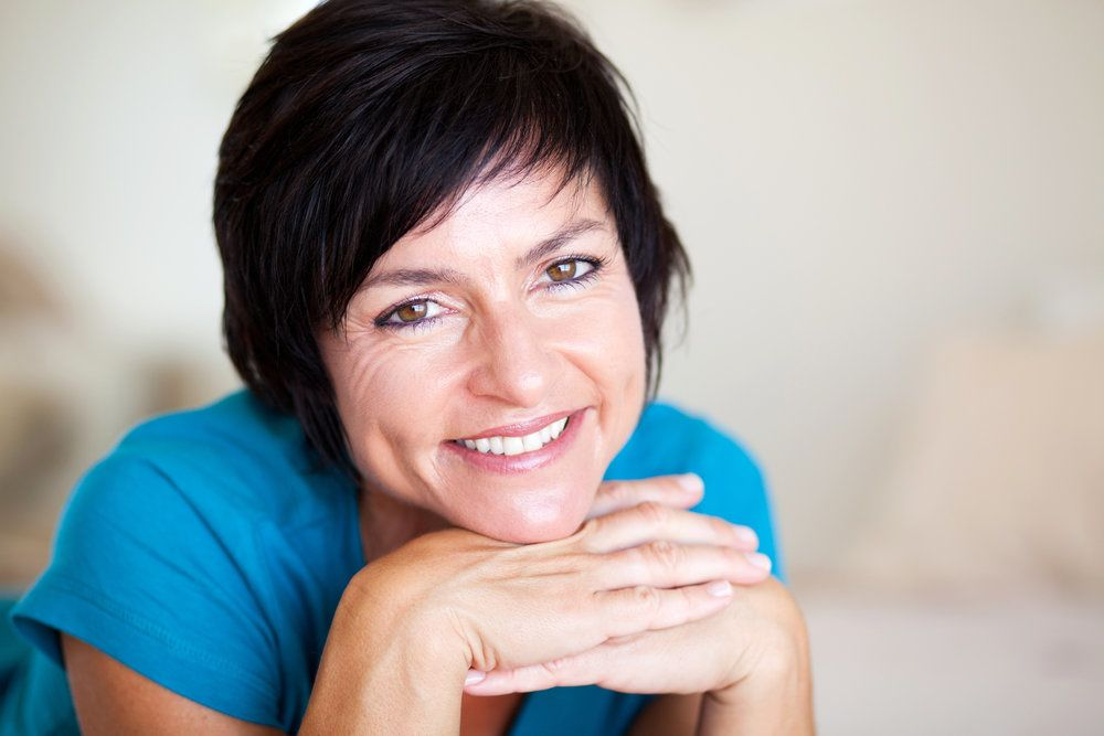 A post-menopausal woman flashing her healthy, radiant smile