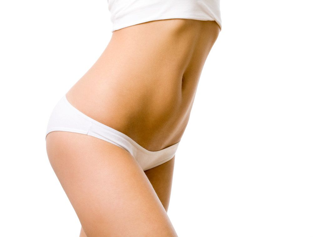 Woman's slim abdomen in white undergarments
