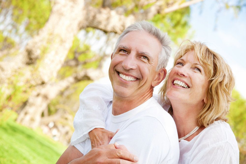 An older man and woman with healthy gums and teeth, smiling