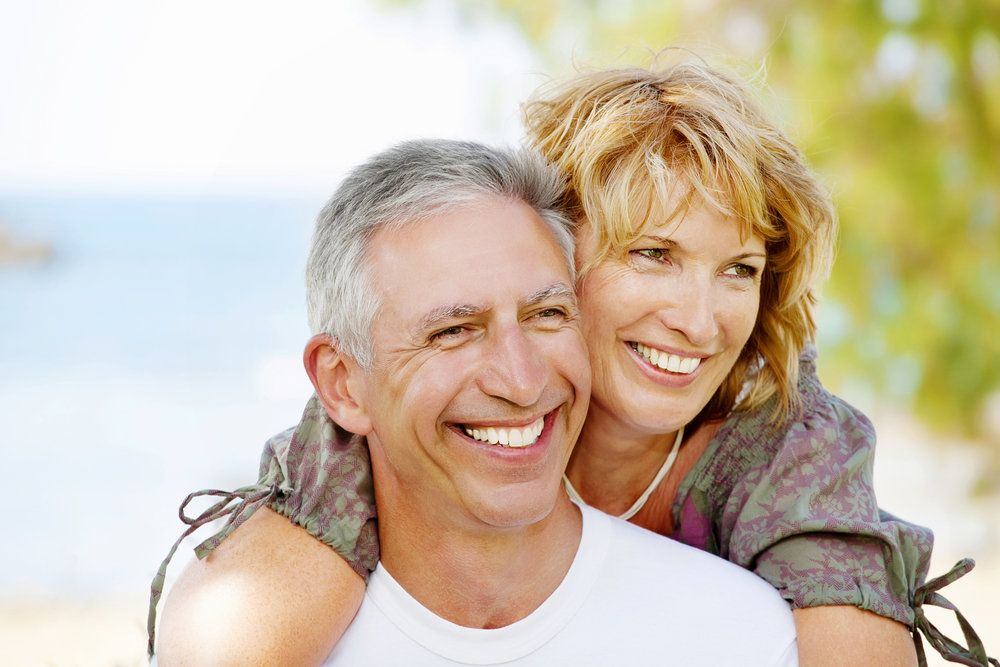 A couple in an embrace, smiling to reveal their healthy mouths, indicative of good heart health
