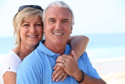 Smiling woman with her arm around a smiling man