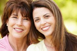 Hispanic mother and daughter with beautiful smiles smiling with heads together