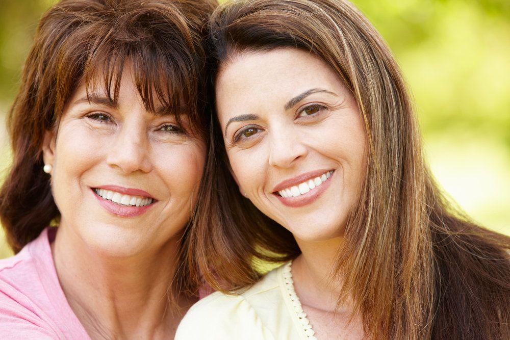 Two women with dental bridges smile