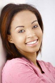 Smiling woman in pink shirt leaning up against wall