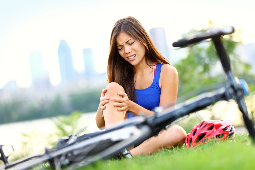 Woman after bicycle crash holding knee in pain