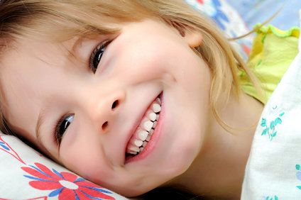 A young girl who is smiling.