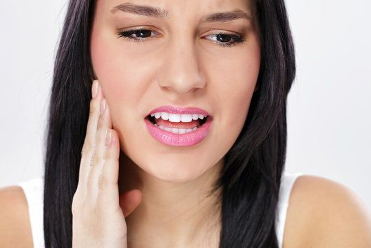 Woman wincing and holding jaw in pain