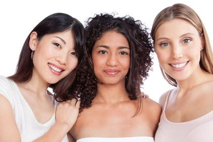 Three smiling women standing closely together