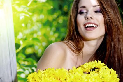 A sultry woman with red hair and purple eyeshadow smiles in front of yellow flowers.