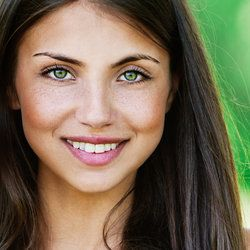 Close up of an attractive young woman whose green eyes are unencumbered by glasses, possibly because she has undergone LASIK surgery
