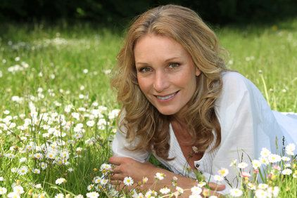 Smiling woman laying on stomach in flower field