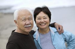 Older asian couple smiling and holding eachother on the beach.
