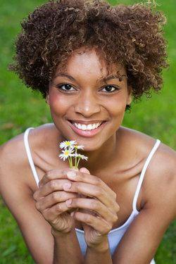 A young woman holding a flower