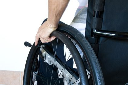 Close-up of a man gripping a wheelchair wheel