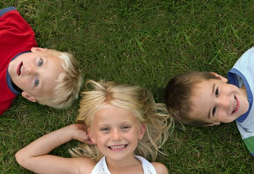 Two young boys and a young girl lying in the grass, smiling happily toward the sky.