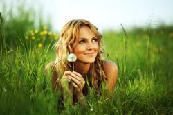 Woman laying in a field while smiling