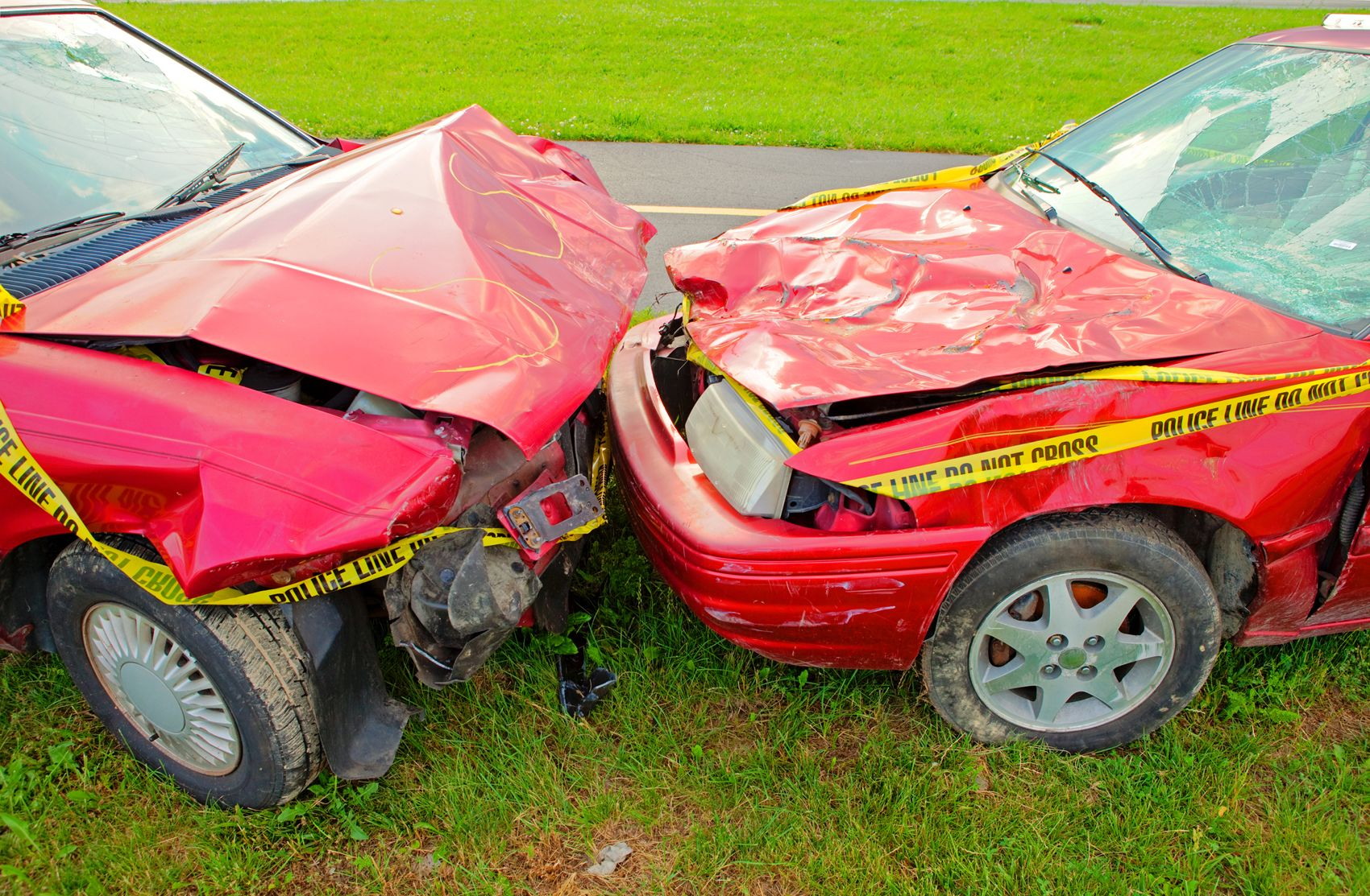 A head-on auto accident with two red cars