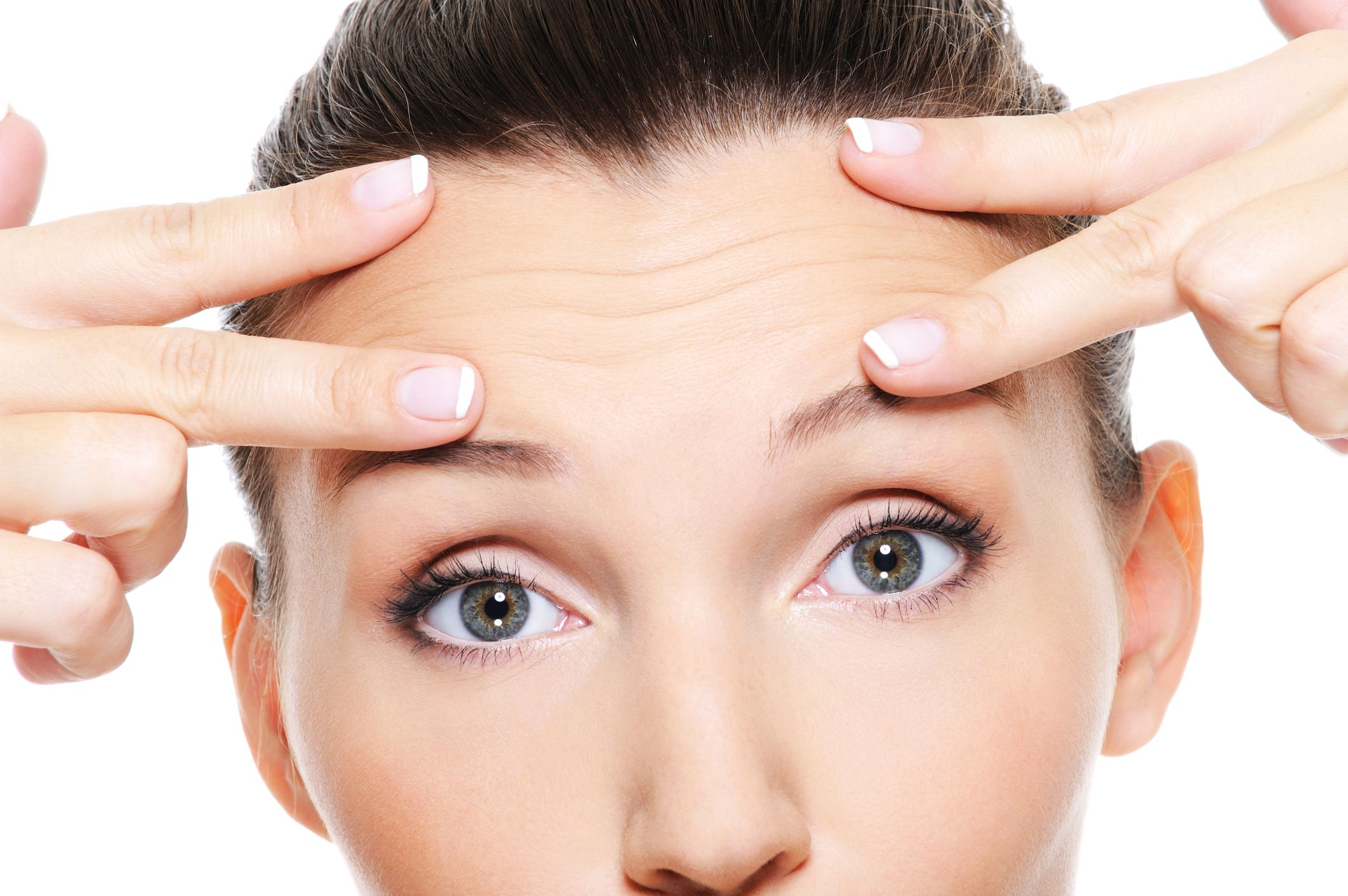 A woman pointing to the wrinkles in her forehead, which could be addressed via a brow lift