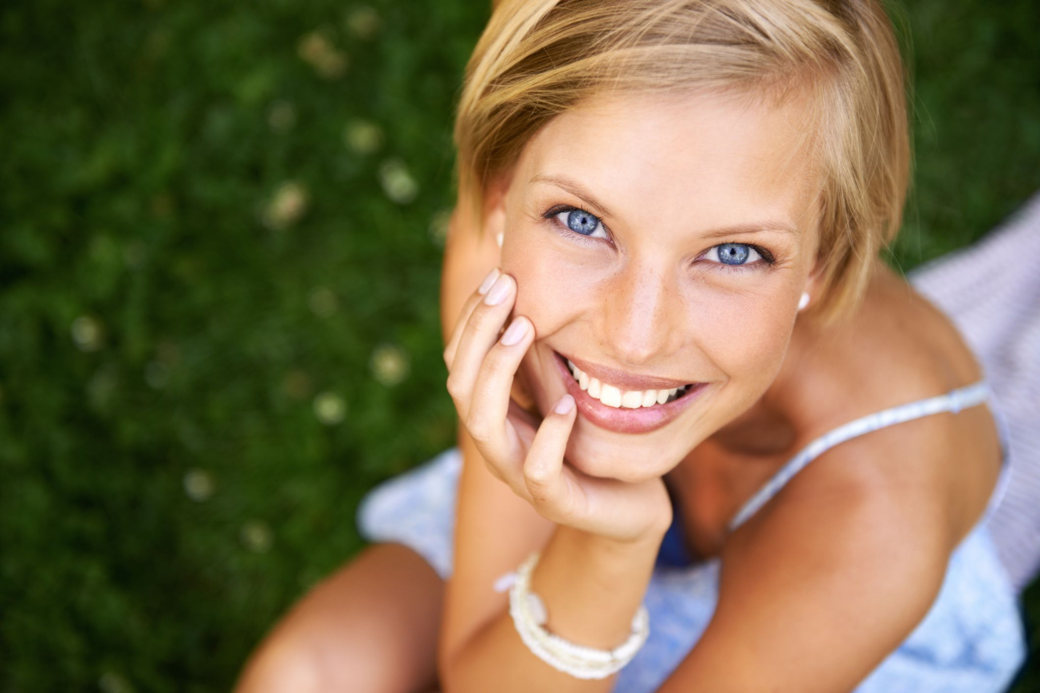 Portrait of smiling blonde woman outside in the green grass