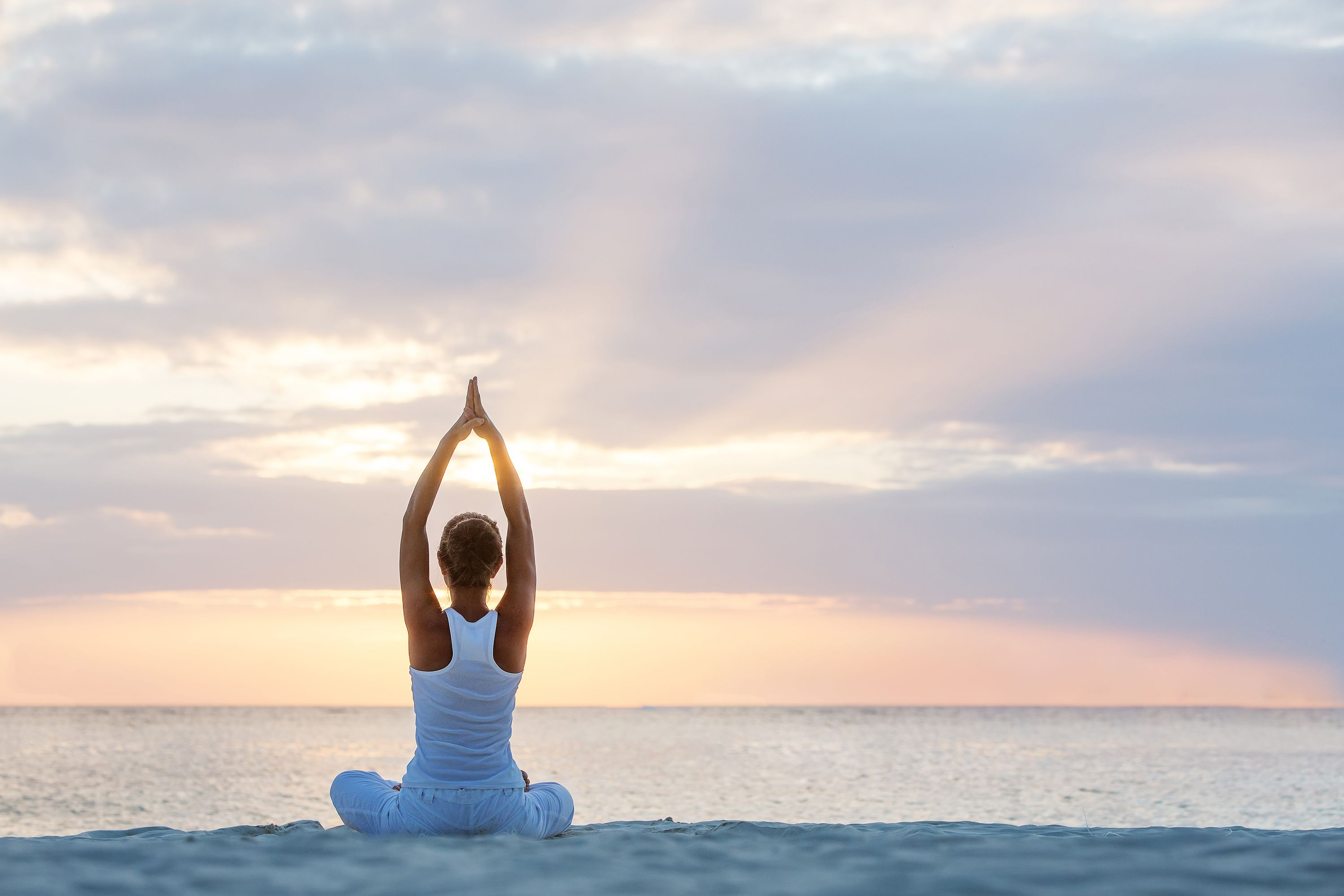 woman dressed in white practicing yoga on the beach