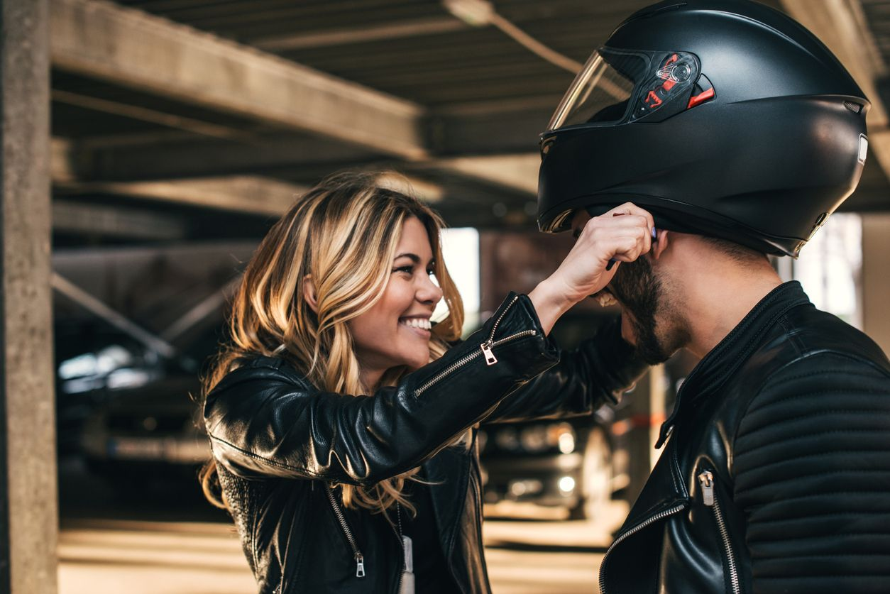 A woman putting a motorcycle helmet on her partner