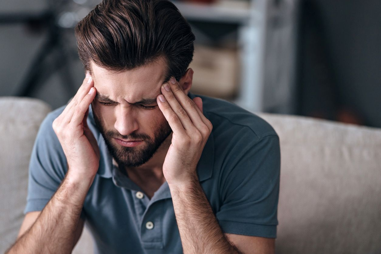 Male suffering from complications of TMJ disorder