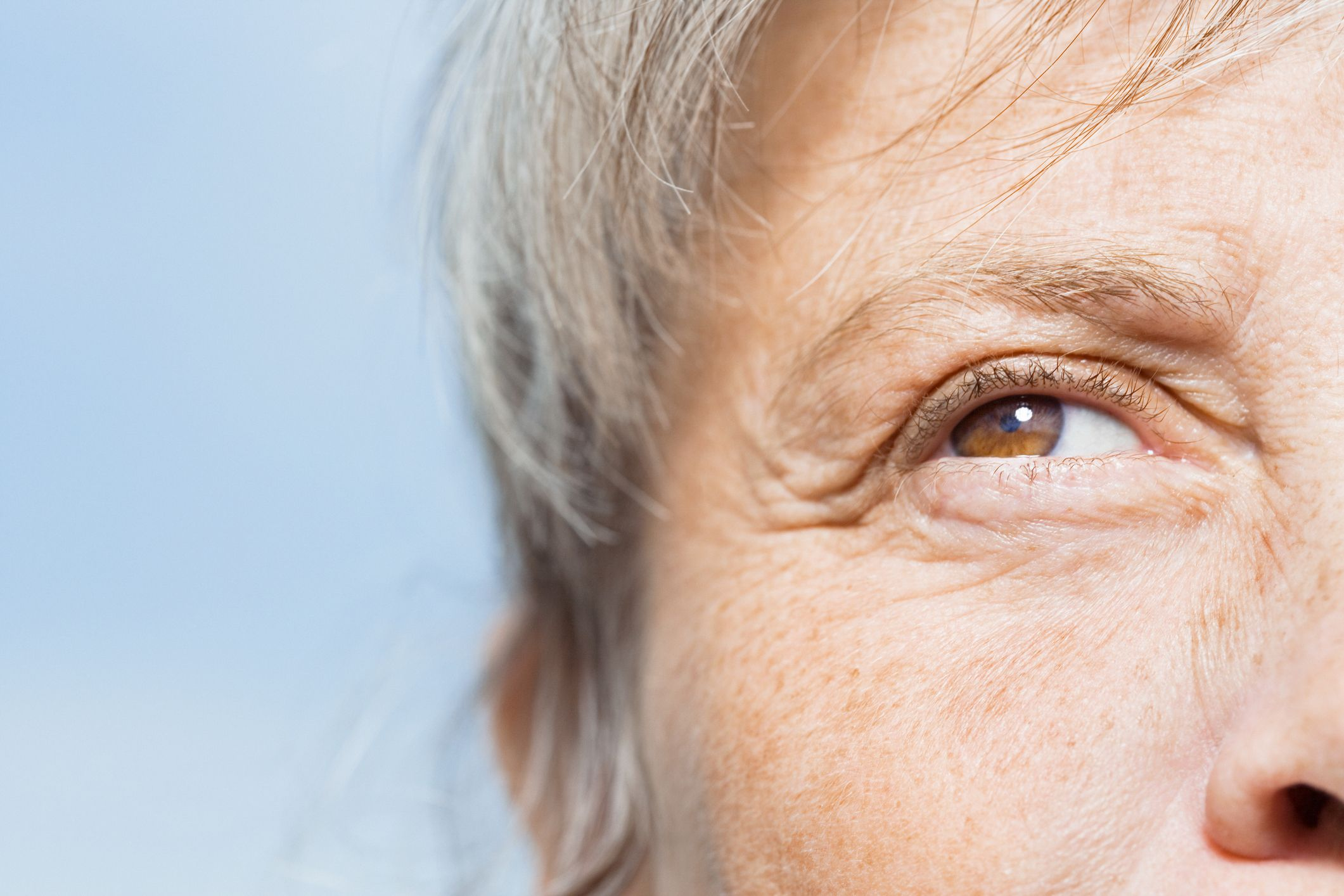 Older woman gazing with wrinkles around eyes