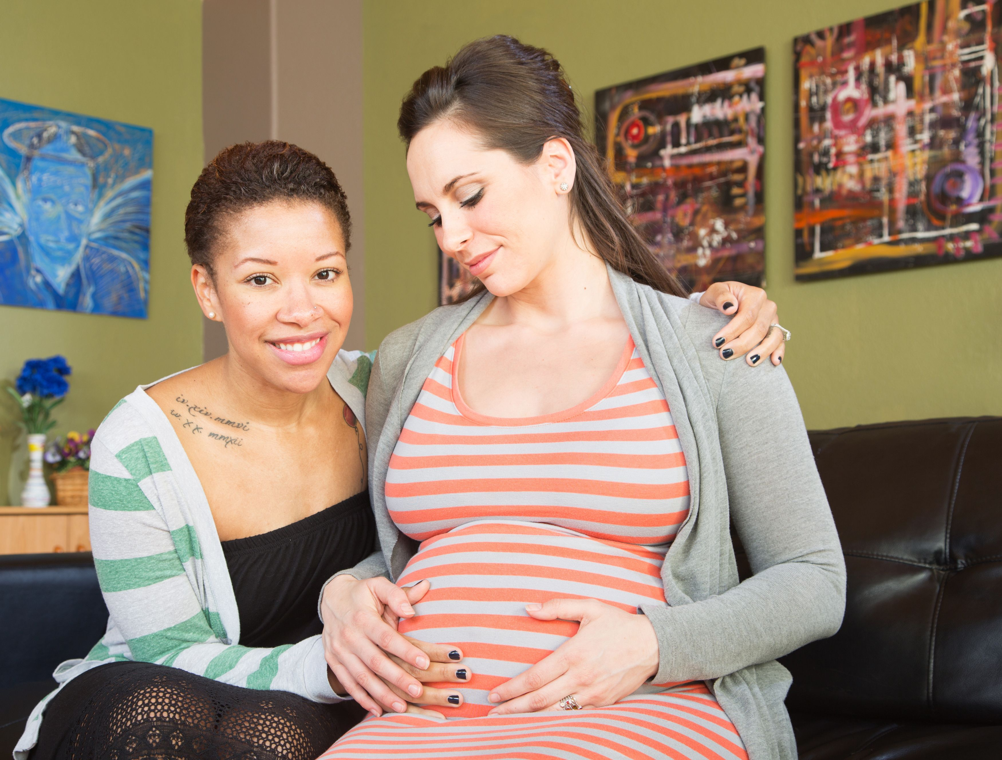 A lesbian couple: a woman with her arm around her pregnant partner