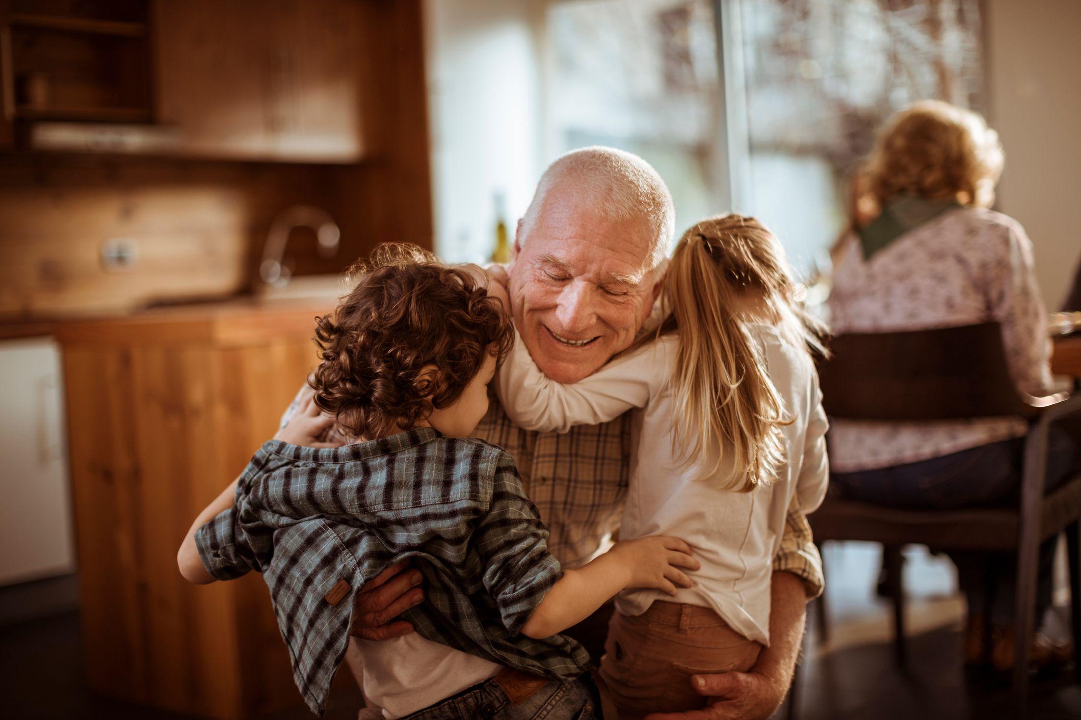 Grandpa hugging two small children