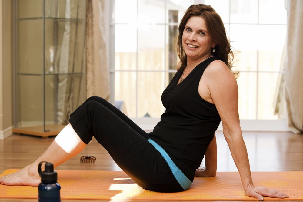 Woman on yoga mat wearing workout clothes