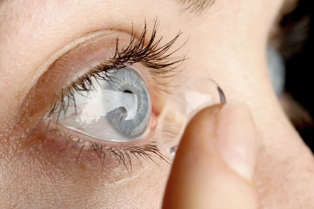 Close-up of a woman placing a contact in the right eye