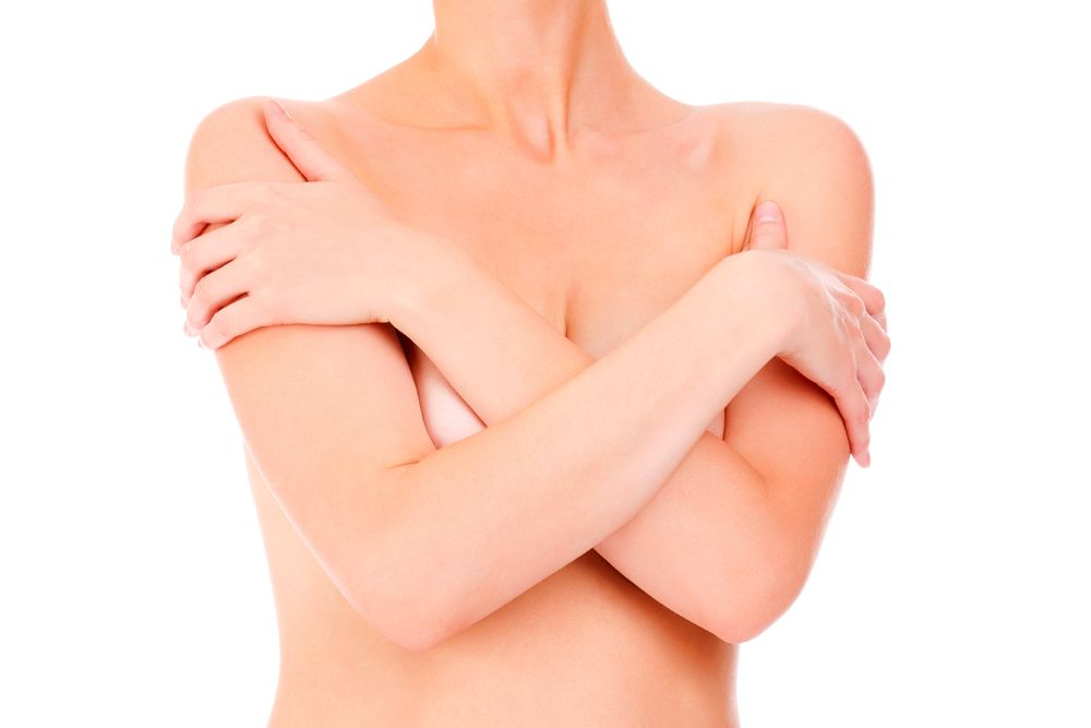 A topless woman with her arms crossed over her breasts