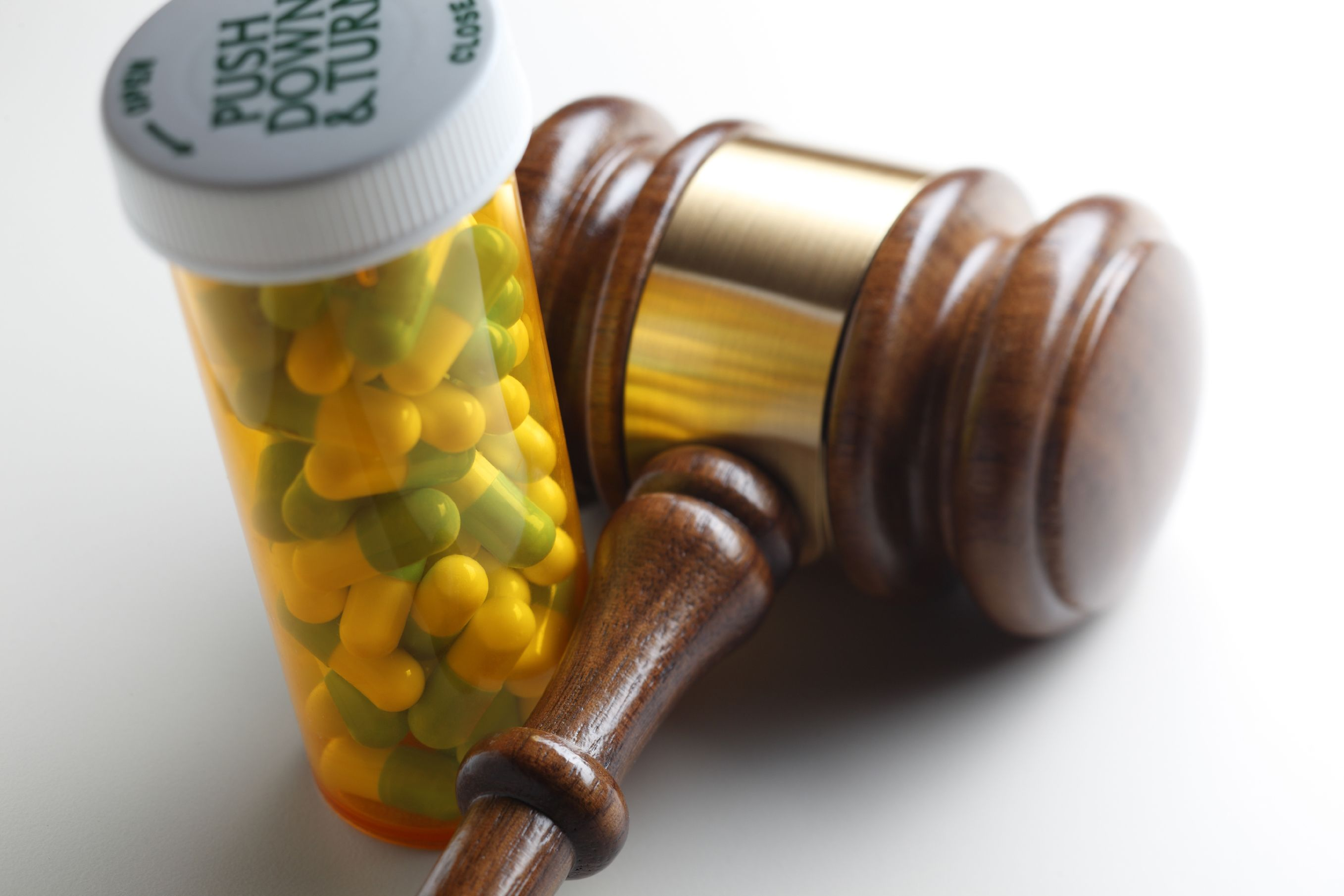 Prescription medication next to a judge's gavel