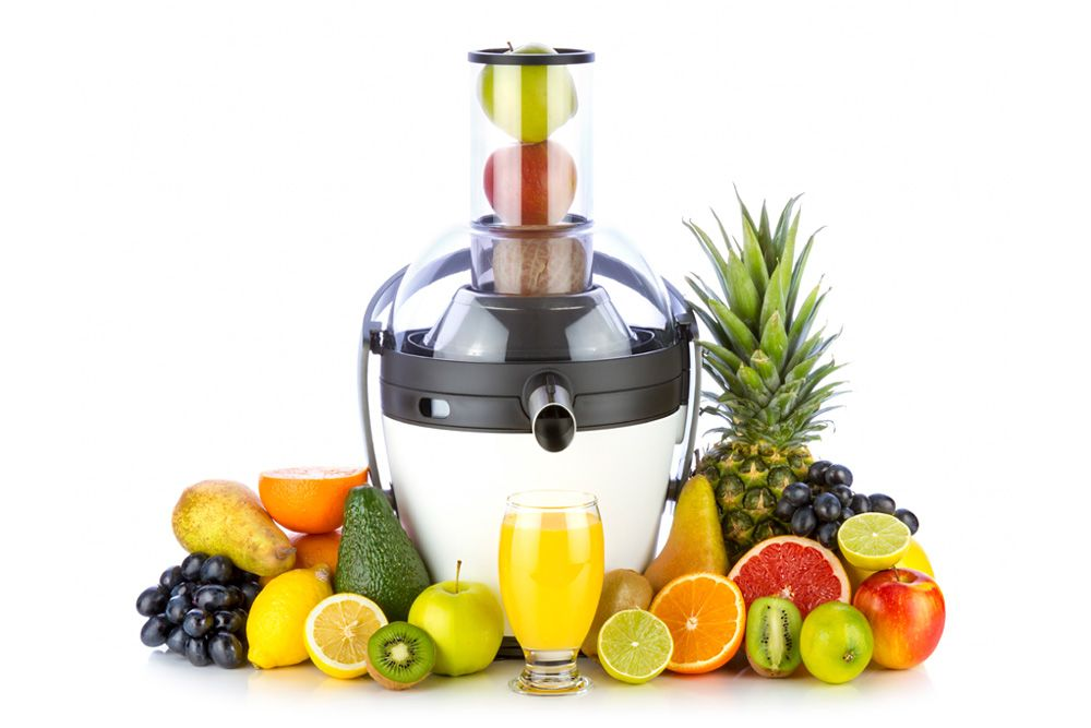 Juicer surrounding by fruits, vegetables and glass of fresh orange juice