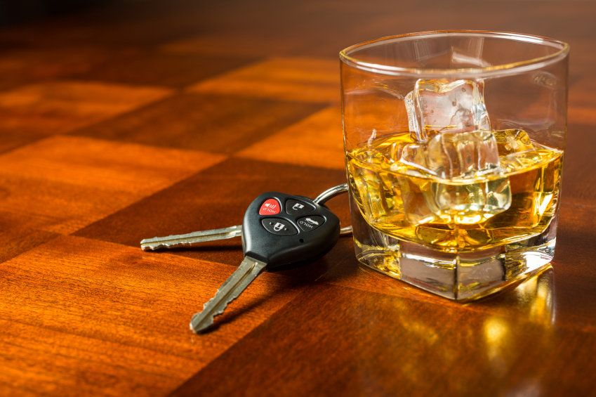 Car keys next to glass of whiskey
