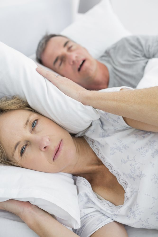 Woman covering her ears while her husband snores next to her