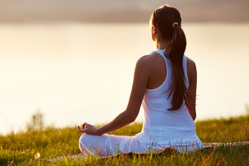 woman wearing white and meditating in a field outside