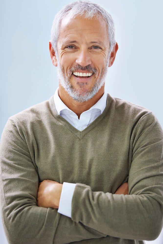 Senior male in grey sweater smiles