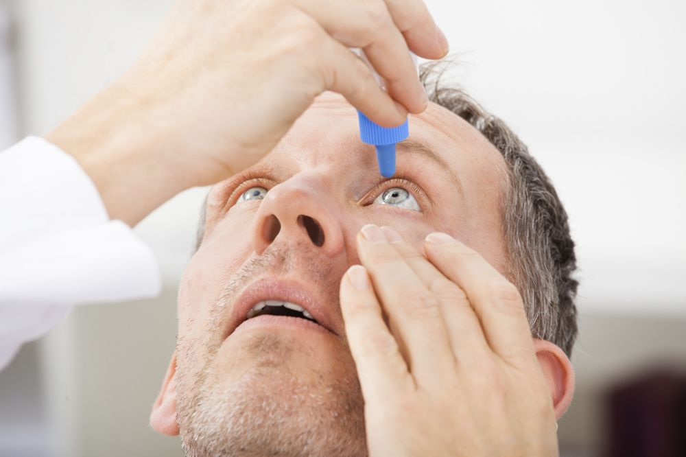 Patient applying eye drops to his eye
