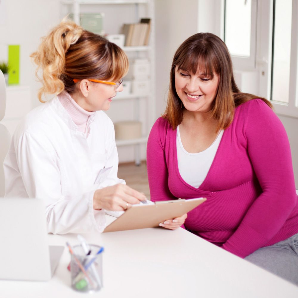 Doctor discussing medical chart with female patient