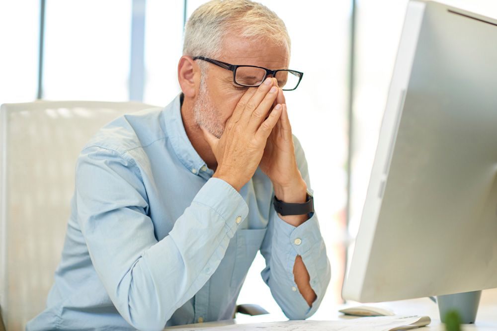 A man rubbing his eyes under his glasses