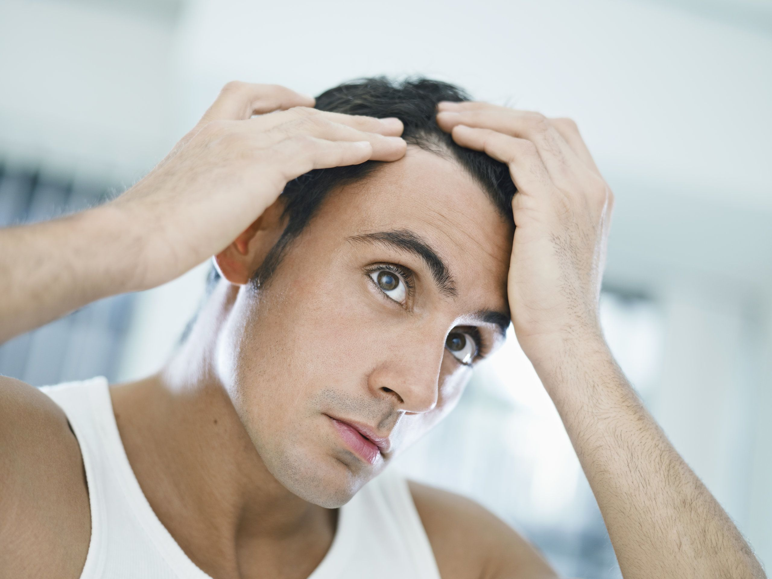 A man examining his hairline