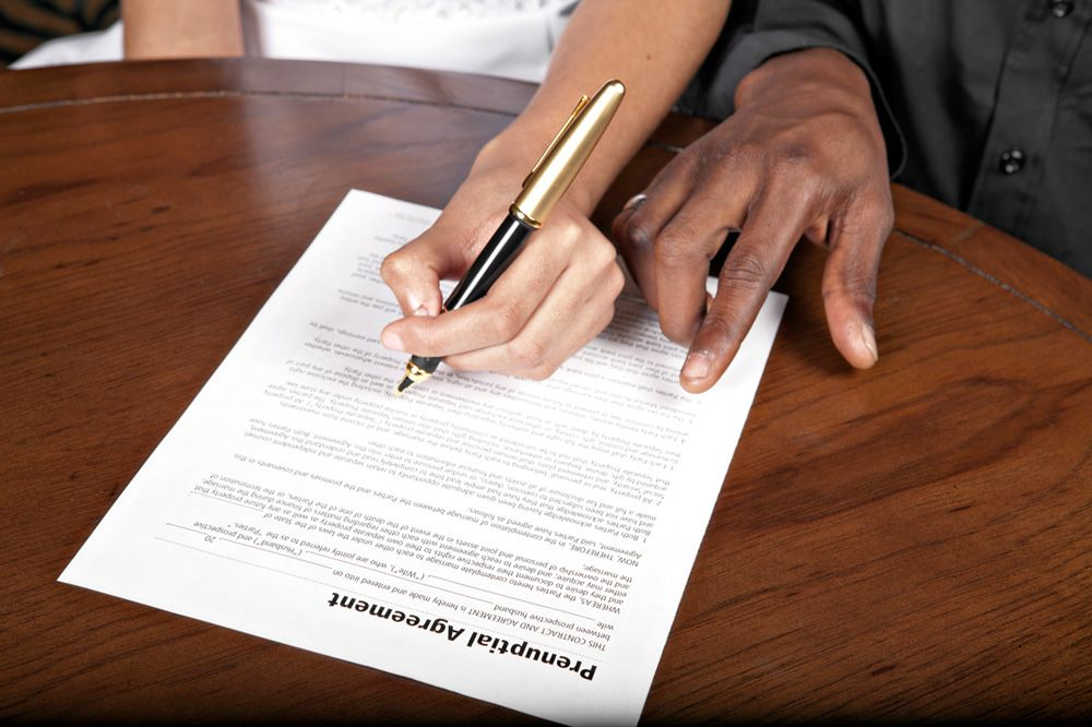 Two sets of hands resting on top of a prenup agreement